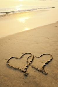 砂浜にハートがふたつ書かれている